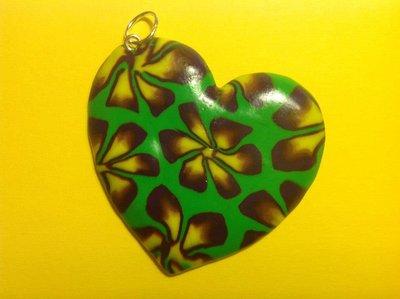 Ciondolo in fimo a forma di cuore su base verde con fiori nei toni del giallo e viola