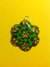 Ciondolo in fimo a forma di fiore su base verde con fiori nei toni del giallo e viola
