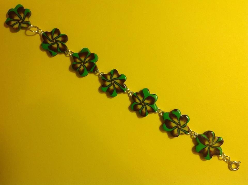 Bracciale in fimo con perle a forma di fiore su base verde con fiori nei toni del giallo e viola
