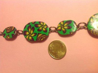 Bracciale in fimo con perle a forma di ovale su base verde con fiori e rose nei toni del giallo e viola