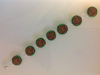 Bracciale in fimo con perle su base verde con fiori e rose nei toni del giallo e viola