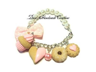 Bracciale con perle bianche, fiocco rosa a pois bianchi in tessuto e cupcake e biscotti in fimo e cernit rosa