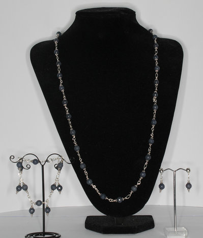 Parure composta da collana, bracciale con charms e orecchini in agata grigia sfaccettata.