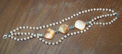 Bracciale home made, sui toni del color salmone, con piccole perle, pietre, perline e distanziatori in metallo