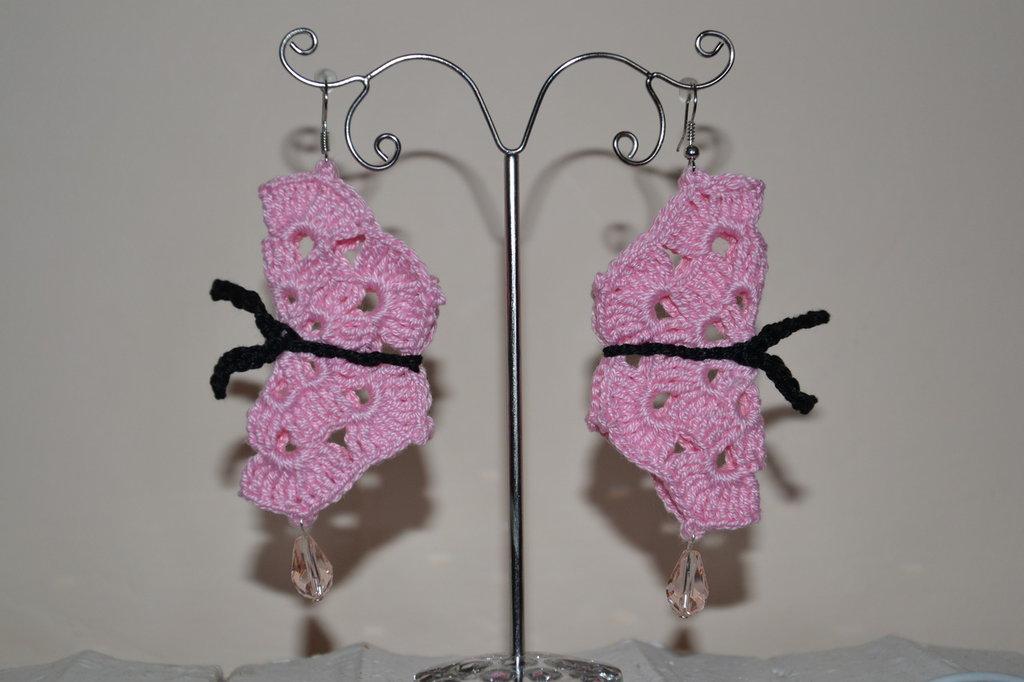 Orecchini rosa a  forma di farfalla.