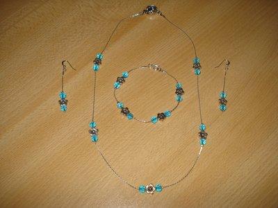 Parure in filo cobra argentato  con mezzi cristalli azzurri e fiore in metallo centrale