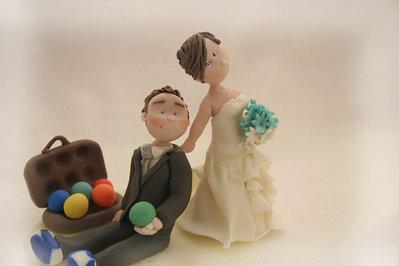 wedding cake topper con sposa che trascina lo sposo amante del gioco delle bocce