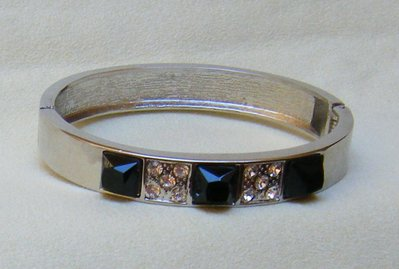 bracciale rigido, con chiusura a molla, in metallo colore argento e strass