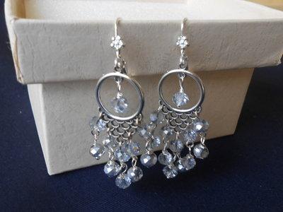 Orecchini chandelier con cristalli grigi.