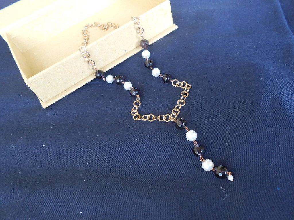 Collana dorata con perle bianche e viola.