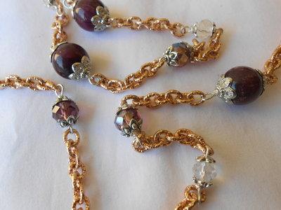Lunga  collana  con agate cristalli e catene dorate.