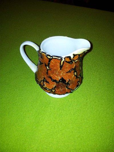 bricco di ceramica rivestito con bucce di arancia