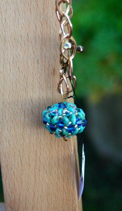 Bracciale dorato con sfera pendente con pietre azzurre, blu, oro e lilla