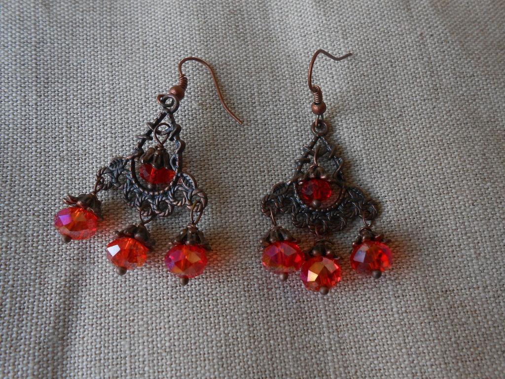 orecchini pendenti fatti a mano in rame con cristalli rossi.