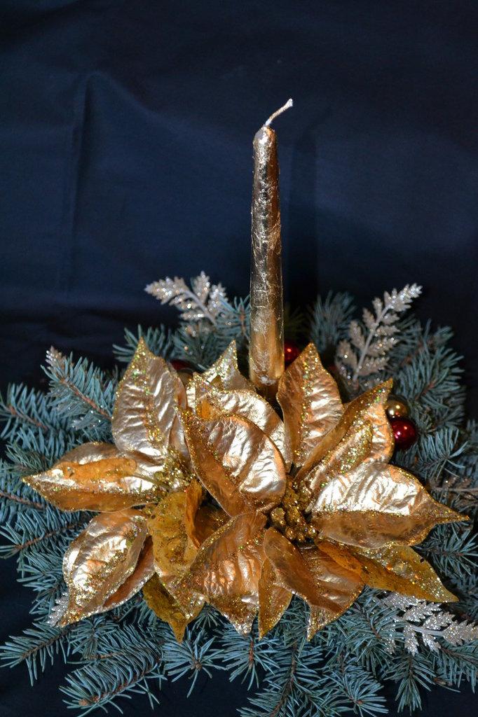 Centrotavola natalizio con stella di natale oro e candela oro