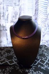 Collana con perle sul viola dentro tubo di rete