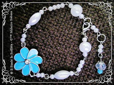 Bracciale con perle e connettore fiore smaltato azzurro con strass centrale.