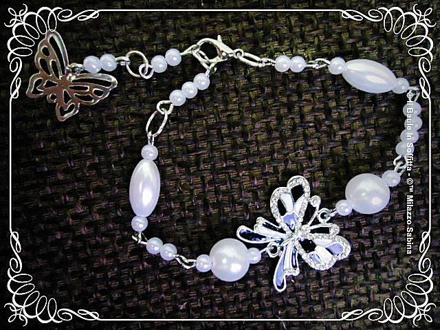 Bracciale con perle e connettore farfalla smaltata bianca e nera e strass.