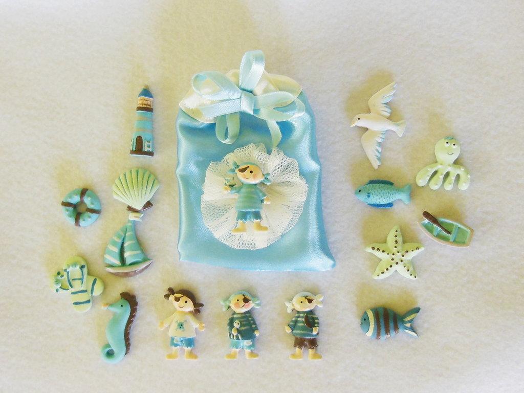 Sacchetti portaconfetti in satin con coccarda in tulle e miniatura a tema marino: per bomboniere dal sapore di mare