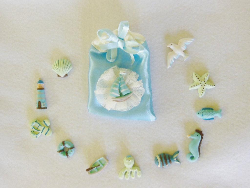 Set di 12 sacchetti portaconfetti in satin con coccarda in tulle e miniatura a tema marino: per bomboniere dal sapore di mare