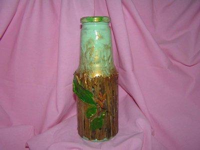 bottiglia di vetro con staccionata di legno e fiore