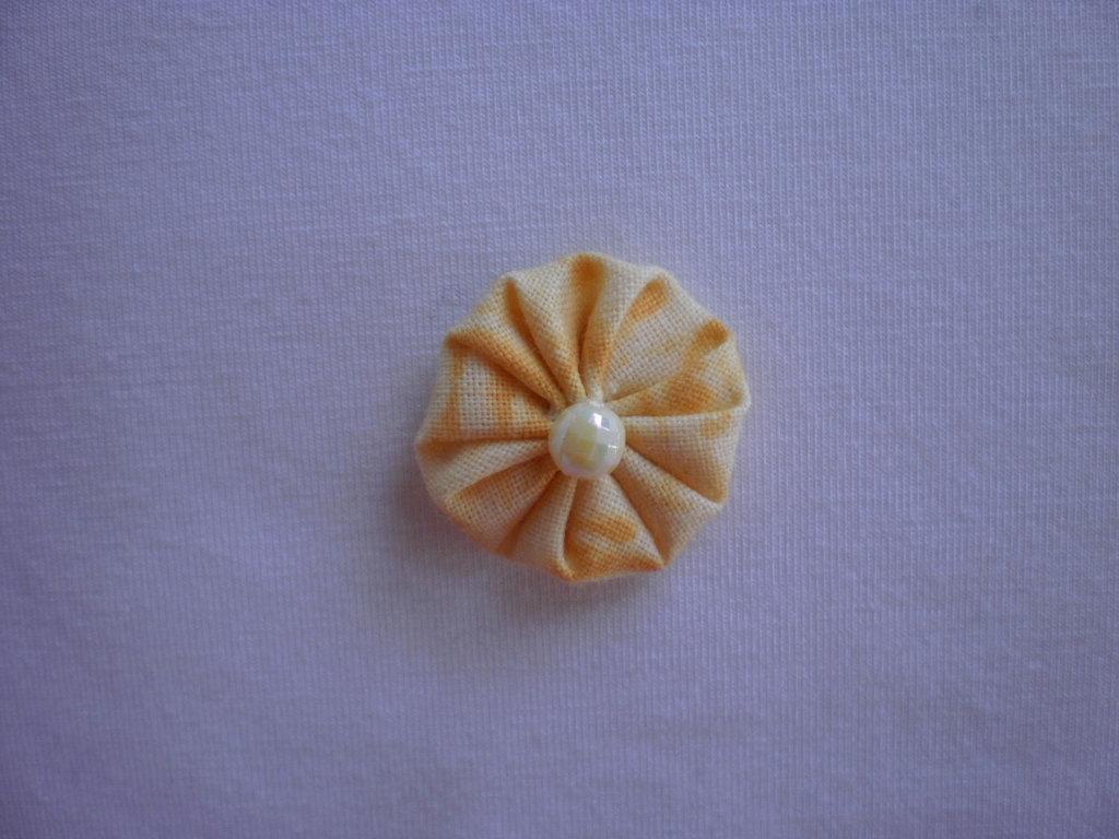 Yo-yo circolare (diametro 3 cm) di stoffa color giallo