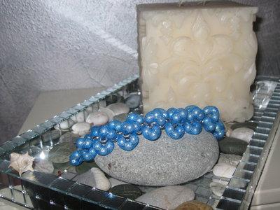 Braccialetto con perle shell inserite nel tubolare a rete azzurra.