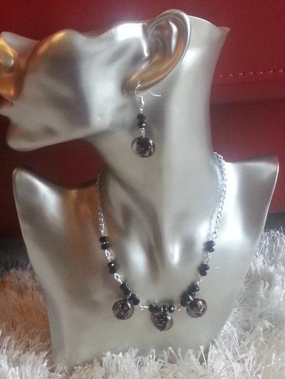collana ed orecchini con pietre trasparenti e nere