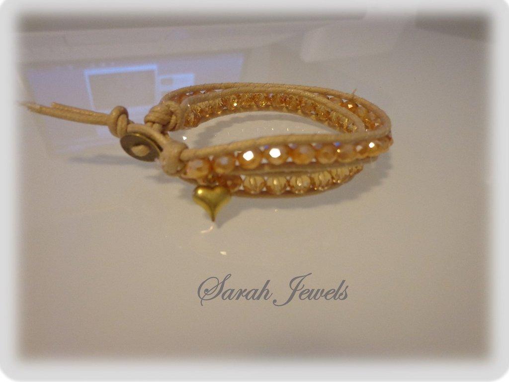 Bracciale moda primavera estate 2014 stile chan luu wrap bracialet doppipo giro cordoncino color naturale e perle color ambra con piccolo ciondolo a formadi cuore sulla chiusira