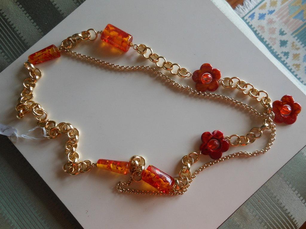 Collana lunga con catena dorata, fiori melange di materiale sintetico, componenti in plastica, colore giallo e rosso screziato.
