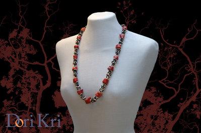 Coralli rossi fatti a mano in una collana medio lunga a catena nera.