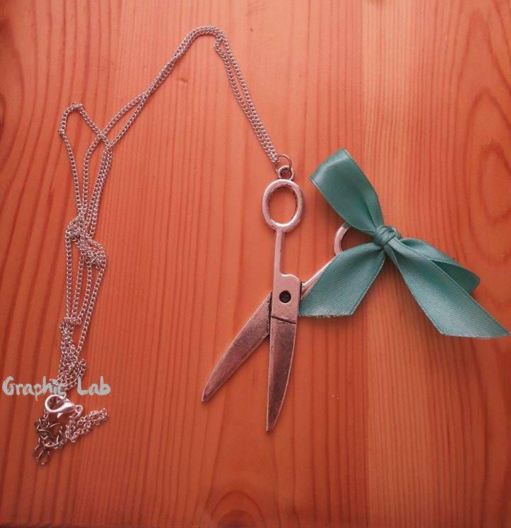 Collana in argento con forbici e fiocco azzurro.