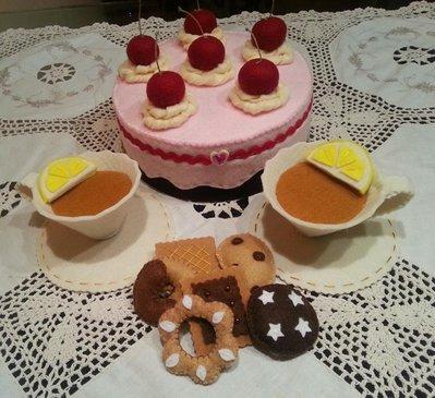 tazze e biscotti in feltro dentro a una scatola a forma di torta