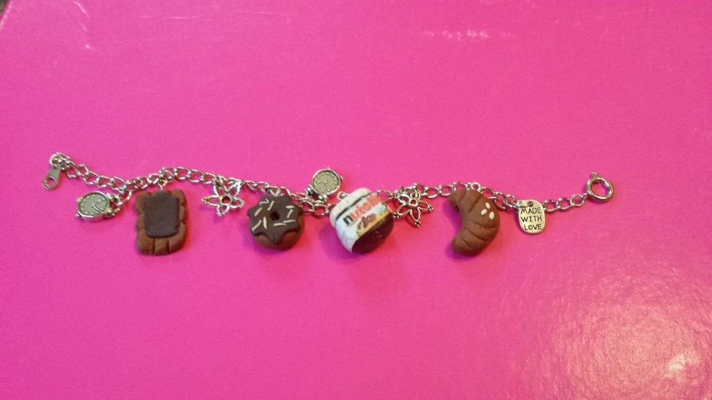 braccialetto in fimo con ciambella con glassa al cioccolato, barattolo di nutella, fetta di pane con nutella e croissant.