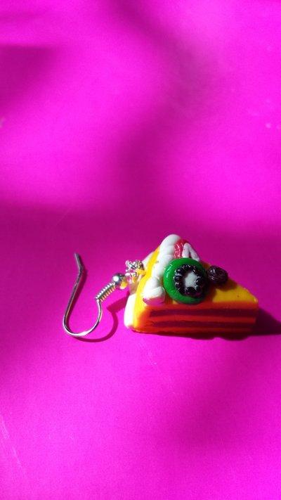 Orecchini pendenti in fimo a forma di fetta di torta ripiena alla frutta: kiwi, fragola e una rosellina al cioccolato; la torta è ripiena di cioccolato e decorata con panna. Con 4 nostri oggetti spedizione gratuita