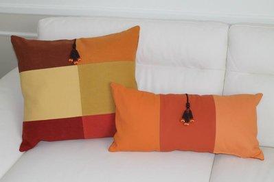coppia di cuscini con nappine marroni in gradazione color arancio