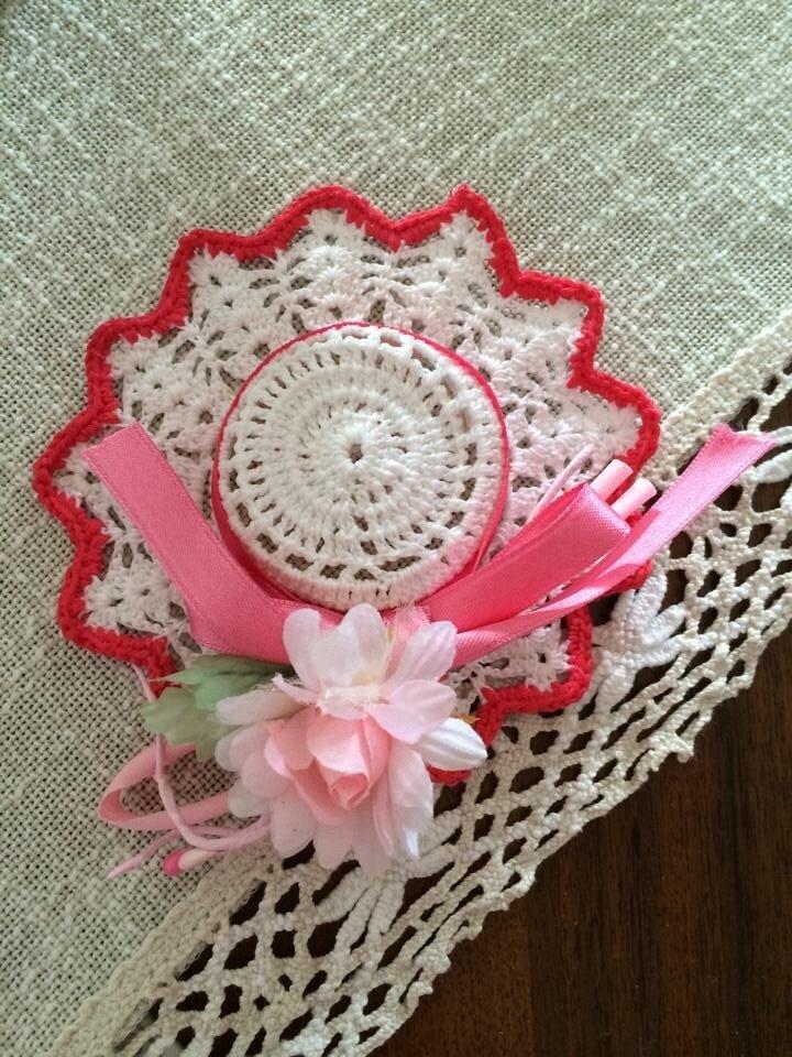 Cappellino fatto ad uncinetto con nastrino rosa con fiore decorativo
