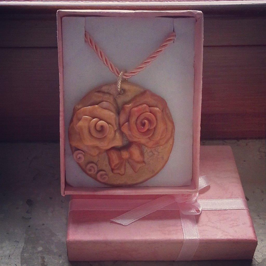 collana con medaglione di rose e fiocco