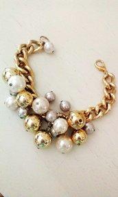 Bracciale catena d'oro e perle di varie dimensioni e colori.