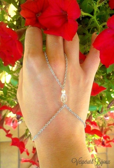 Eleganti Fingerbracelet con perlina trasparente a goccia.