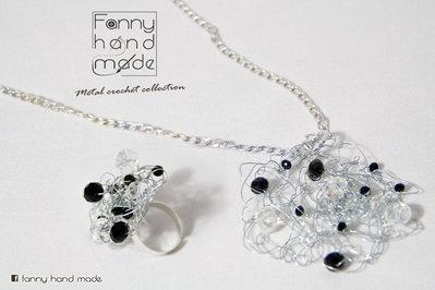 Parure ciondolo e anello in filo di metallo color argento con perle nere e bianche.