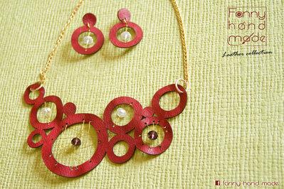 Parure - Collana in pelle rossa intagliata con decoro in filo metallico d'ottone con orecchini abbinati.