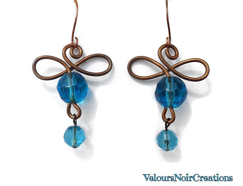 Orecchini simbolo infinito in rame e perle in vetro azzurro