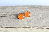 Orecchini in resina a pois bianchi su sfondo arancione, perfetti per l'estate.