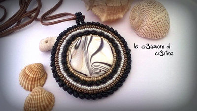 Medaglione etnico con madreperla striata, perline bianche, nere, bronzo