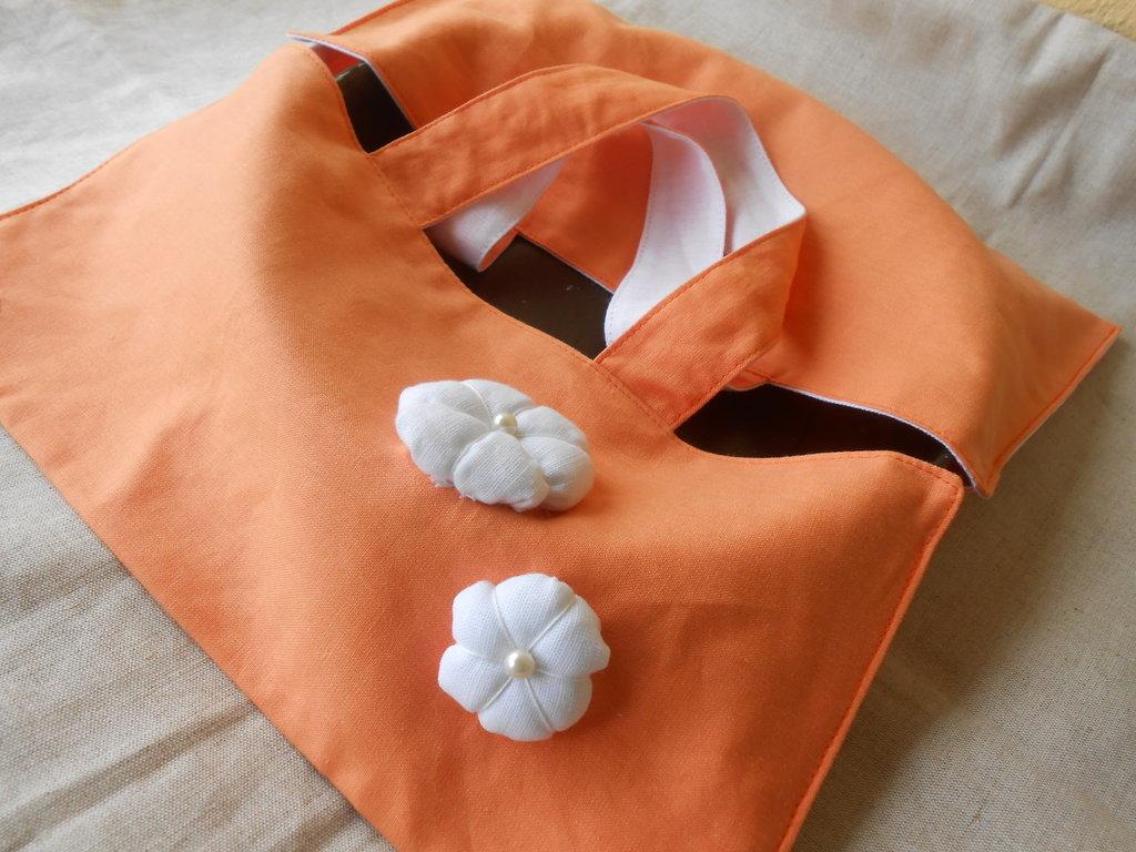 Borsa   portatorta in lino arancio con interno e fiori bianchi.