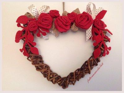 Cuore di rametti intrecciati con rose rosse
