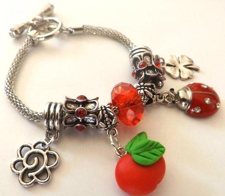 Bracciale con base in metallo,perla rossa,elementi con strass,ciondoli portafortuna e mela in fimo idea regalo!!