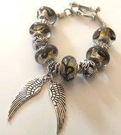 Bracciale con base in metallo,perle nere con riflessi dorati,distanziatori argentati e ciondoli a forma di ali idea regalo