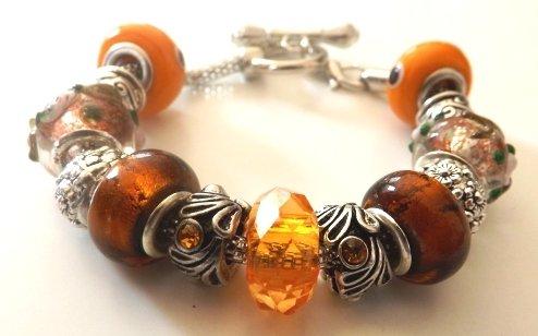 Bracciale con base in metallo,perle a foro largo nei toni dell'arancione  ed elementi in argento tibetano idea regalo